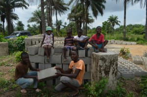 A few of Marth's children at the building site with the bricks that have been donated.